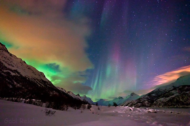 Sterne, Nordlicht und Mond hinter Wolken