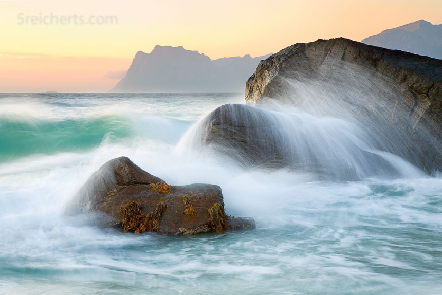 eine etwas längere Belichtungszeit zeigt den Weg, den die Welle am Felsen nimmt. Die sanften Abendfarben unterschreichen den Eindruck, dass das Wasser den Felsen sanft streichelt.