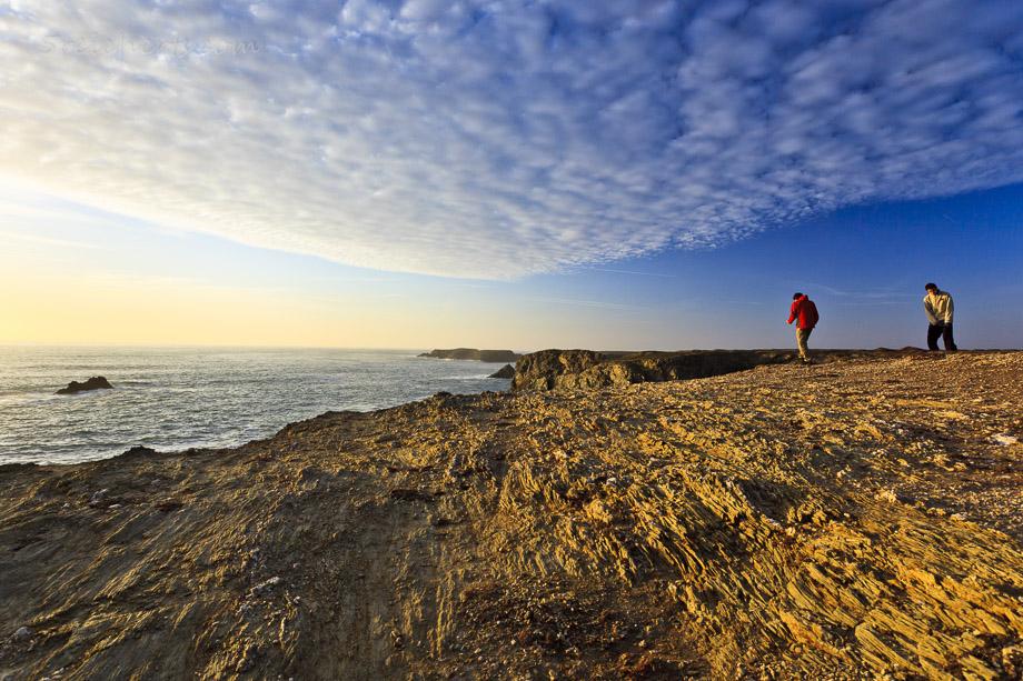 Esra und Noah klettern über die Felsen in der Nähe von Port Coton, Belle Ile