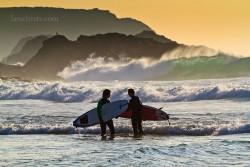 zwei Herren treffen sich in seichten Wasser nach dem erfolgreichen Ritt auf der Welle