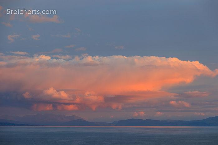 eine Wolke regnet im Abendlicht ab