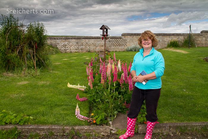 Sheila im Garten vor dem Leuchtturm - in manchen Jahren wächst dort gar nichts meint sie