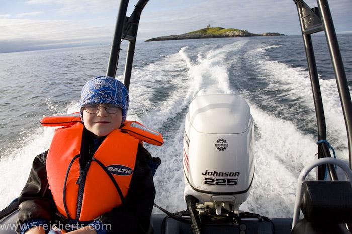 Amy glücklich auf dem Meer - im Hintergrund, die Insel mit dem Leuchtturm