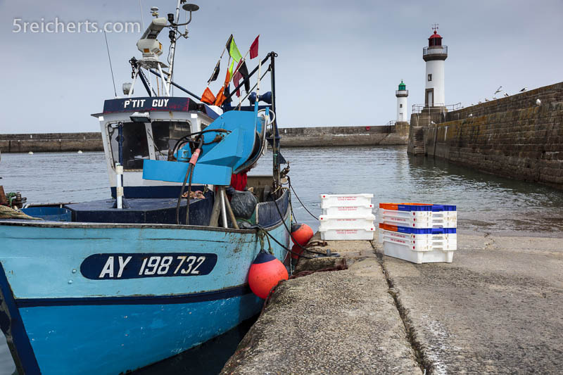 Ein Fischer putzt seinen Fang direkt auf dem Boot im Hafen von Le Plais, Belle Ile, Bretagne