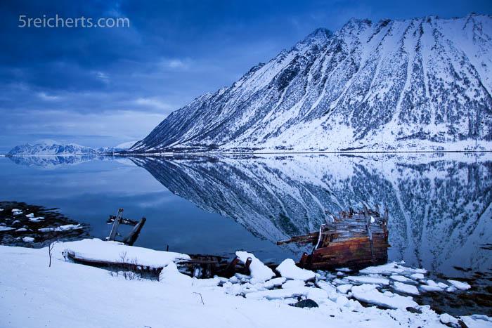 reste eines Bootwracks im norwegischen Fjord, Winterliche Berge, Lofoten