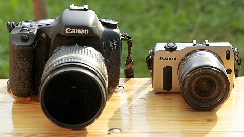 Ein Größenvergleich der Canon EOS M mit der Canon EOS 7D. Der Zoombereich der Objektive ist in etwa gleich