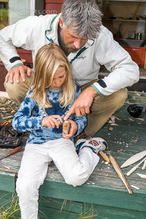 Vater und Tochter beim Schnitzunterricht