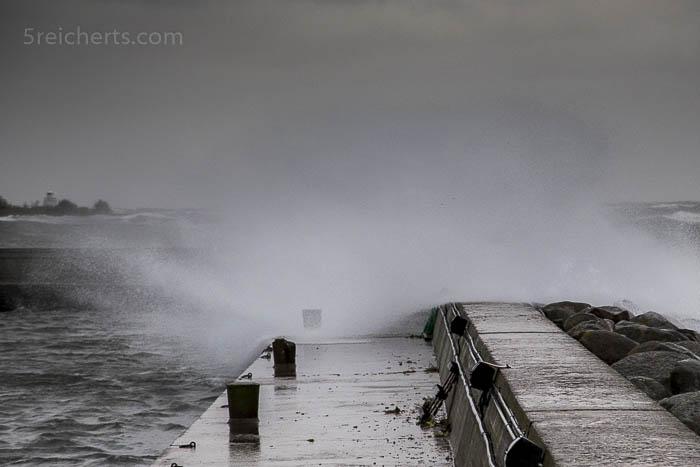 Die Wellen wehen über die Hafenmauer