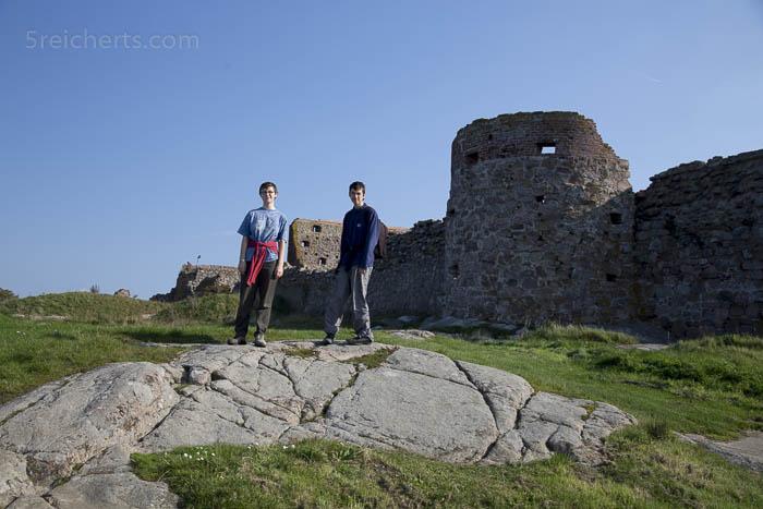 Amy und Noah auf abgeschliffenen Gletscherfelsen, die Burgruine Hammerhus im Hintergrund