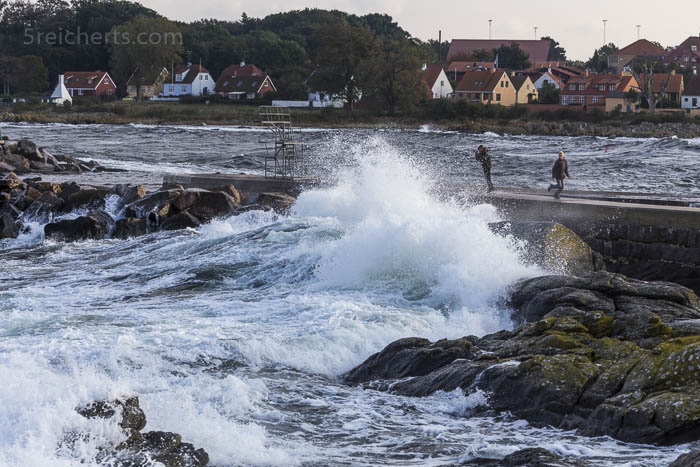 Kinder spielen mit den Wellen