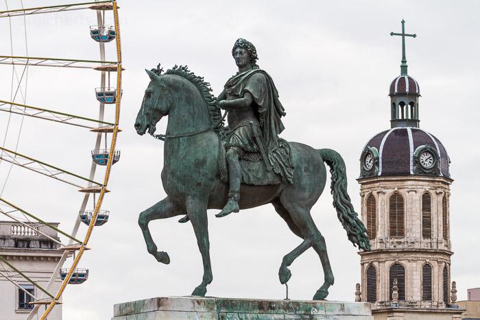 Denkmal von Louis XVI auf dem Place Bellecour. Das Tele rückt Denkmal, Kirche und RIesenrad dicht aneinander. 1/100 sec. f/8, ISO 200, 141 mm Brenneweite.