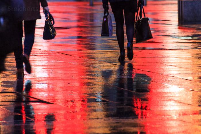 Shopping in der Nacht. Schaufensterlicht spiegelt sich auf nassem Asphalt. 1/20 sec. f/5.6, ISO 2000, 240 mm Brennweite.