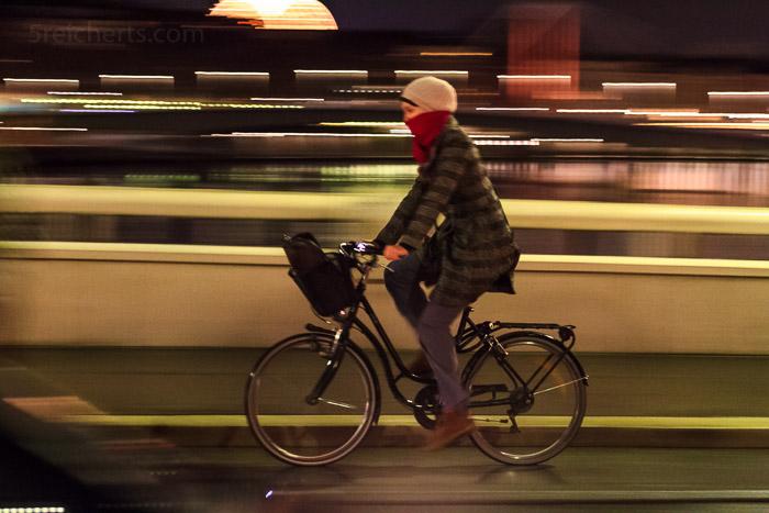 Radfahrer auf Saone-Brücke. 1/10 sec. mitgezogen, f/5.6, ISO 5000, 70 mm Brennweite