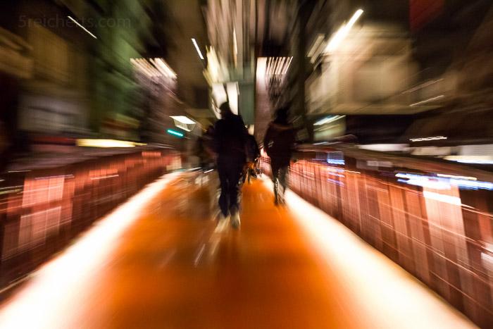 Fussgängerbrücke in der Nacht. Während der Belichtung gezoomt. 1/3 sec. f/11 ISO 5000, 81 mm Brennweite