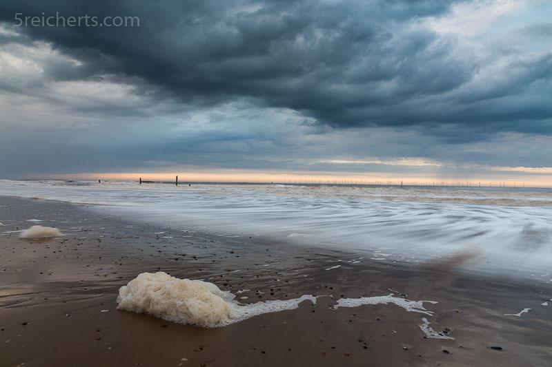 schaumige Wellen und Regenwolken
