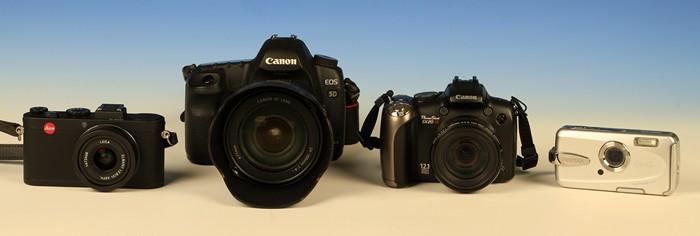 Links eine Edelkompakte mit Festbrennweite, die teuerste im Quartett, daneben eine digitale Spiegelreflexkamera, die größte und schwerste der vier. Als nächstes folgt eine Superzoom-Kompaktkamera mit dem größten Brennweitenbereich, und ganz rechts die silberne Kompaktkamera ist wasserfest, staubfest und kann sogar tauchen.