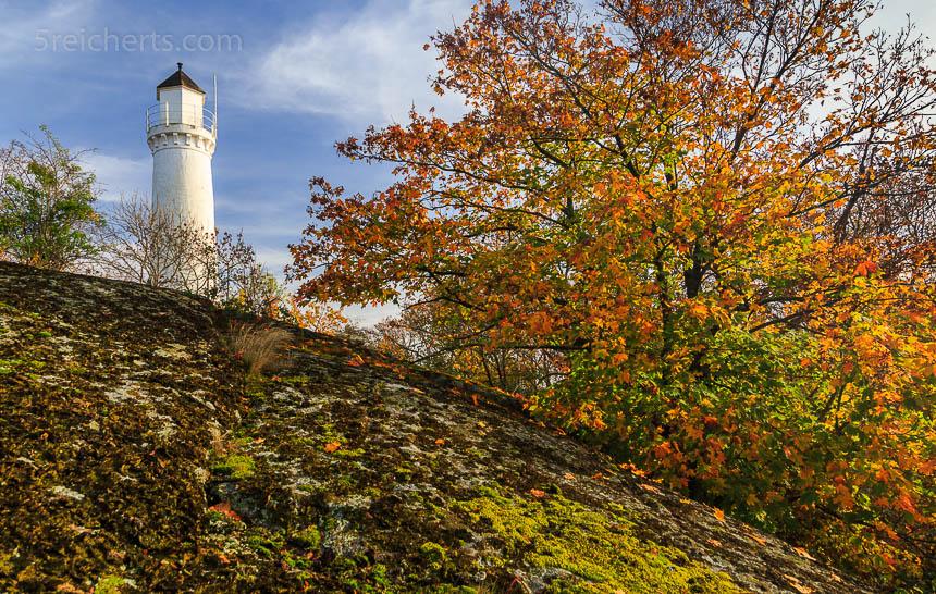 Der Leuchtturm sitzt oben in der Ecke. Bildbestimmend sind der flechtenbedeckte Granit und der Herbstwald, die viel über den etwas ungewöhnlichne Standort des Turms verraten.