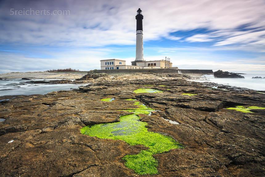 Vordergrund, Linienführung. Die grünen Algenbecken bilden eine Zickzacklinie, die den Blick auf den Leuchtturm lenkt.