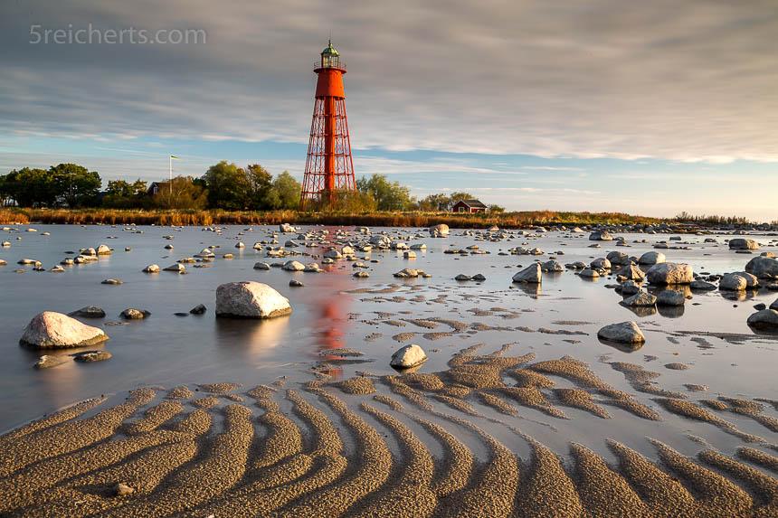 Seitenlicht, Linienführung. Das Licht des späten Nachmittags zeigt platisch Leuchtturm, Steine und Sand.