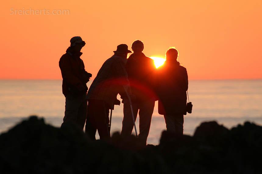 Gegenlicht bei Sonnenuntergang. Nur die Silhouetten der Personen sind erkennbar.