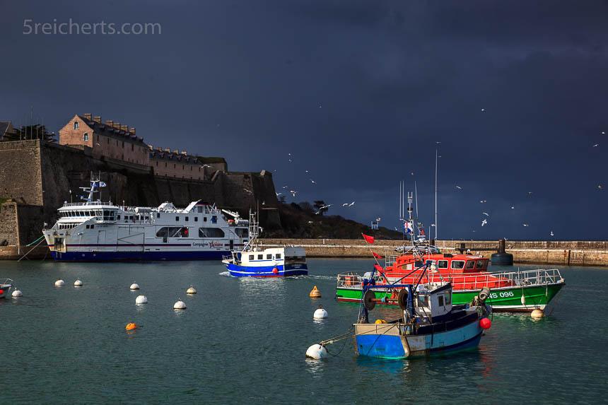 Der Hafen liegt zwar in der Mittagssonne, aber die aufziehenden Regenwolken verleihen dem Bild dramatische Wirkung.