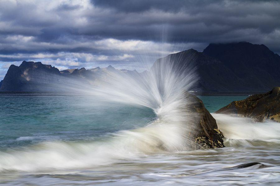 In Myrland auf den Lofoten trifft eine Welle auf den gleichen Felsen, nur wurde diesmal mit 1/4 Sekunde belichtet. Die wegfliegenden Tropfen ziehen Linien, es ist als ob die Welle explodieren würde.