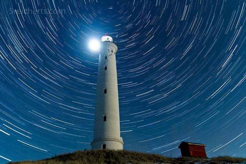 Die Sterne ziehen ihre Bahnen, während der Leuchtturm, fest verwurzelt in den Dünen, sein Licht weit hinaus aufs Meer wirft.