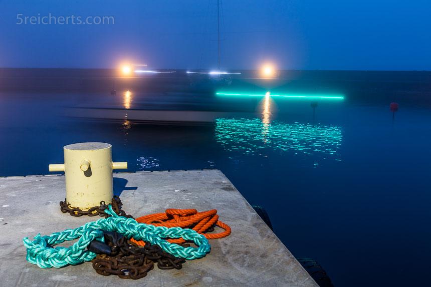 Nachts an der Hafeneinfahrt. 8 Sekunden mit Stativ, dadurch ist das Boot nur noch schemenhaft erkennbar.