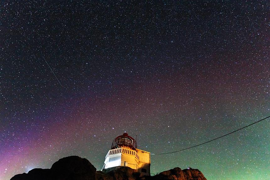 Leicht rotes Nordlicht und Sternenhimmel
