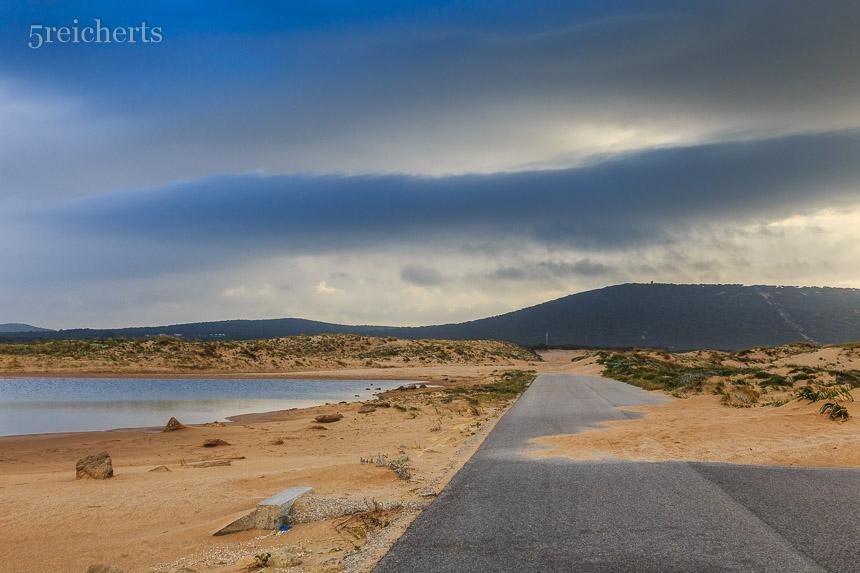 Sandverwehungen auf der Zufahrtsstraße zum Leuchtturm, Andalusien
