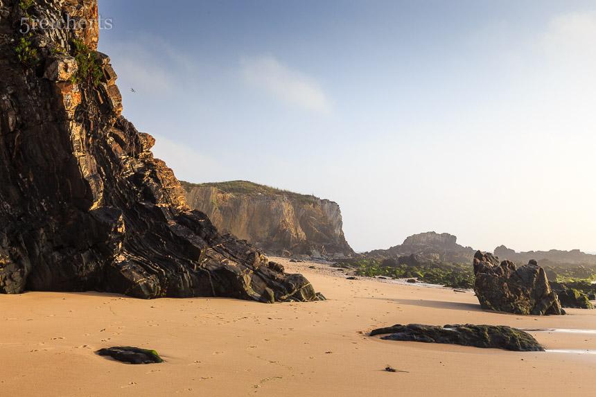 Eine der sandigen Buchten mit der gewaltigen Steilküste