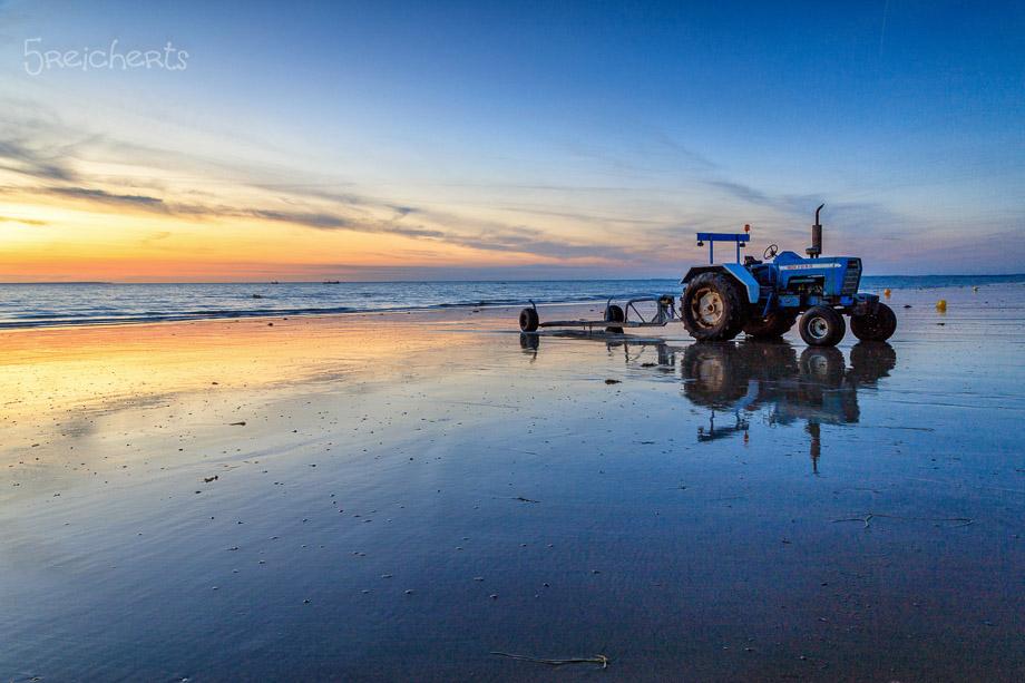 Sonnenuntergang und Traktor am Strand von Gouville