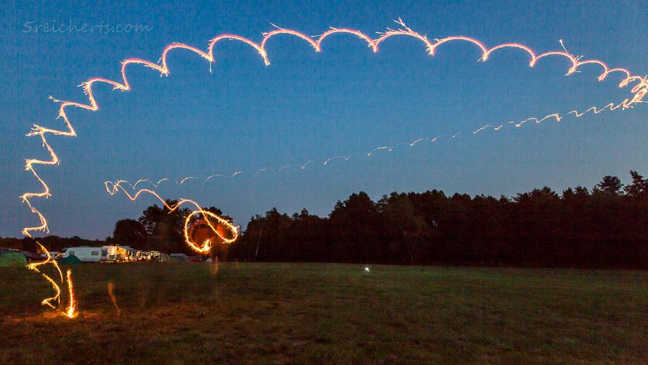Nachtaufnahme von einer Bumerang-Flugkurve. Die Lichtspur kommt von einer angeklebten Wunderkerze