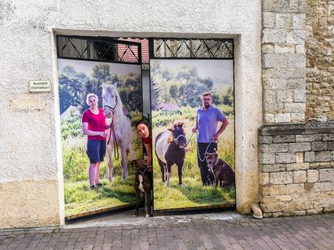 Myriam und Mario mit ihren Tieren und den Fotos am Tor