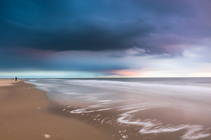 Seichte Wellen am Strand als Kontrast zu den Wolken